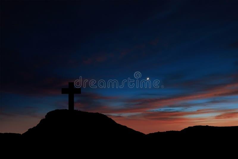 一个十字架的剪影在山的在日出 库存图片