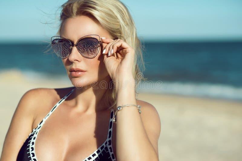 一个华美的白肤金发的在海滩的夫人和游泳衣的画象被反映的太阳镜的 Eyewear概念 免版税库存图片