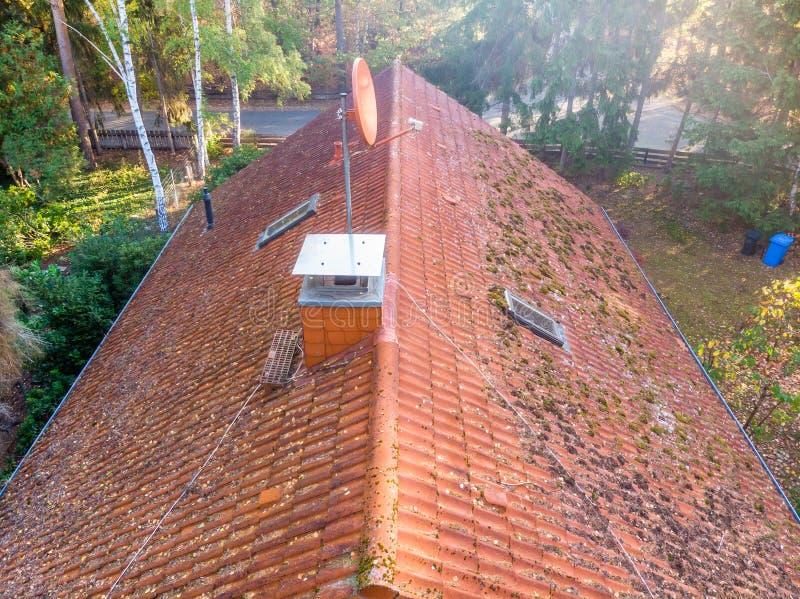 一个单身家庭的房子的红瓦顶的检查,瓦片的情况的检查在屋顶的分隔 免版税库存图片