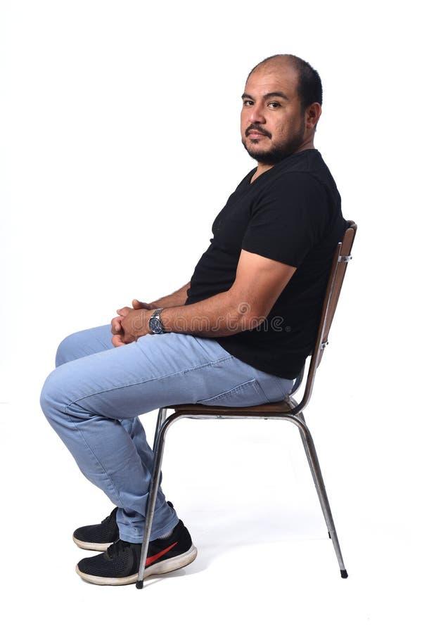 一个南美人的充分的画象坐在白色的一把椅子 库存图片