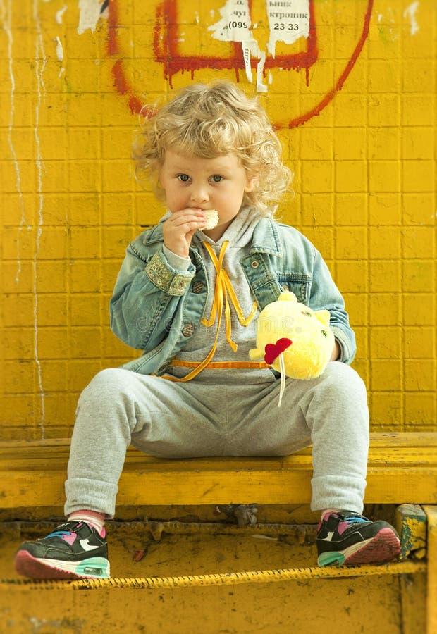 一个卷曲女孩坐在公共汽车站 免版税库存图片