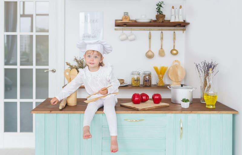 一个厨师盖帽的小女孩有在面孔的一副鬼脸的坐桌用苹果 库存图片