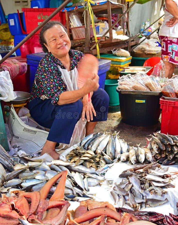 一个友好的泰国供营商在一个湿市场附近的曼谷上的卖干鱼 免版税库存图片