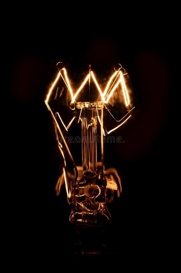 一个发光的电灯泡的钨细丝在黑暗的背景的 库存照片