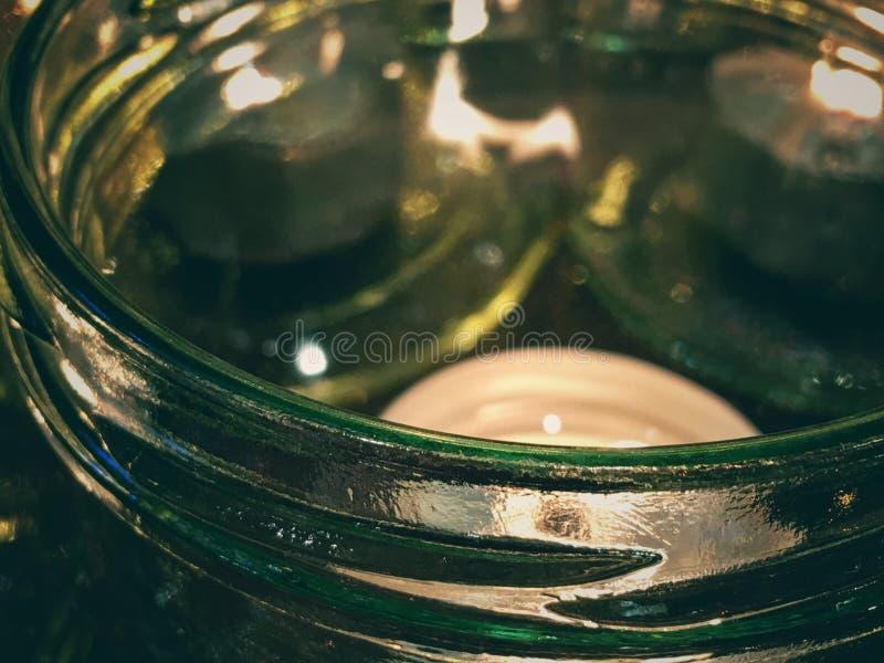 一个发光的绿色玻璃瓶子的外缘有灼烧的茶光蜡烛的 库存照片