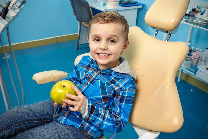一个口腔外科的年轻男孩与aplle在他的手上 免版税库存照片