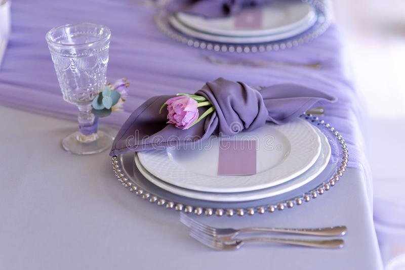 一个古典婚礼的壮观的餐桌装饰品在淡紫色颜色的 免版税图库摄影