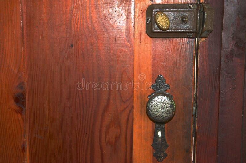 一个古板的锁、门把手和死的螺栓在一个木门 库存图片
