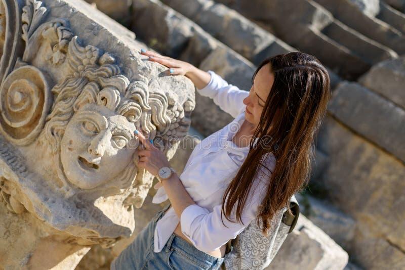 一个古老罗马城市的废墟的妇女游人探索和接触古老建筑学的在代姆雷,土耳其 库存照片