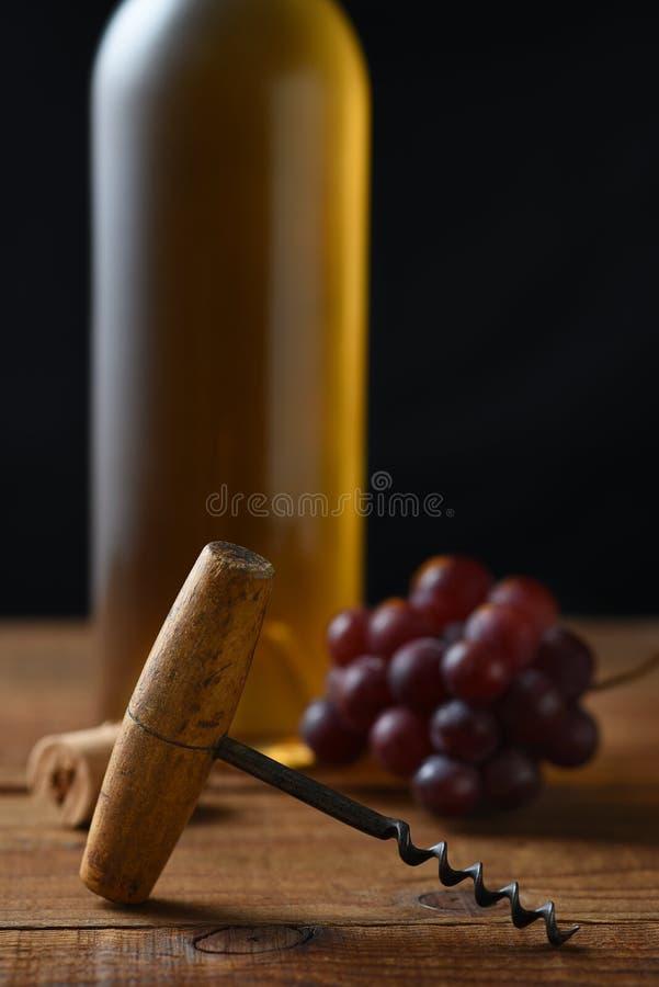 一个古色古香的黄柏螺丝用在焦点白酒酒瓶葡萄外面和黄柏的特写镜头在背景中 图库摄影