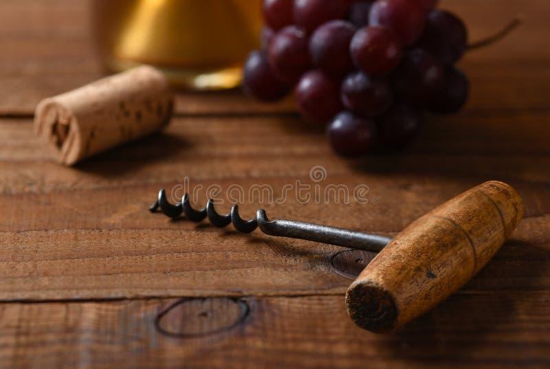 一个古色古香的黄柏螺丝的特写镜头有在焦点黄柏、葡萄和一个瓶的白酒外面在背景中 免版税库存照片