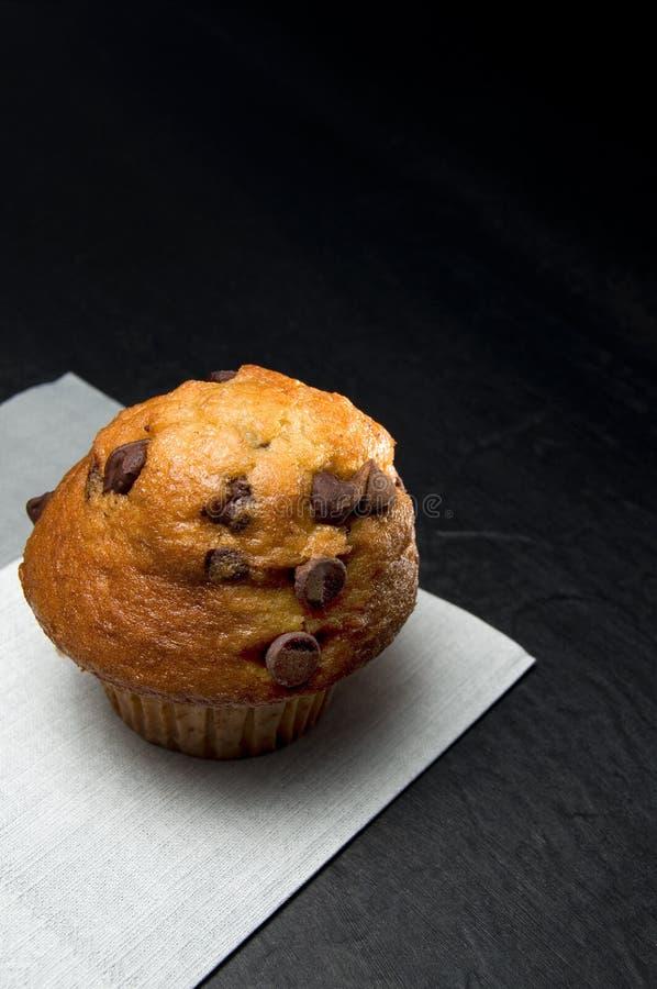一个可口巧克力片松饼的接近的看法与灰色餐巾的在黑暗的背景 库存照片