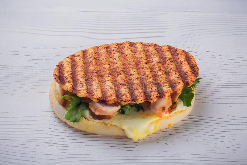 一个可口自创烤三文鱼汉堡用沙拉和调味汁 免版税库存照片