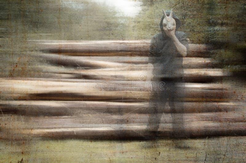 一个可怕,奇怪,戴头巾图,拿着兔子面具对他的面孔 在堆旁边注册有弄脏的一个森林,难看的东西,vint 免版税库存照片