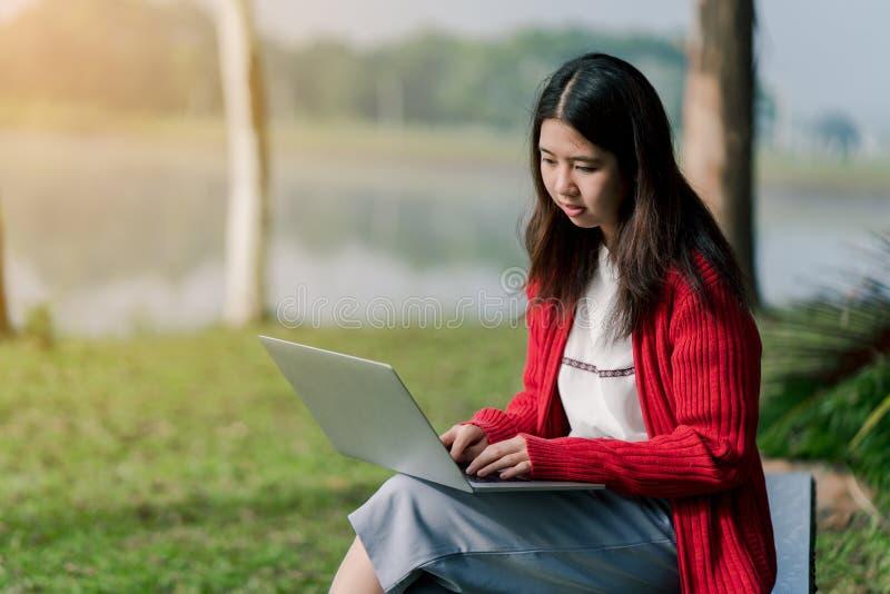 一个可爱的亚裔女孩是聪慧在旅游区 有一手提电脑在路的手上在雾中 后面是  图库摄影