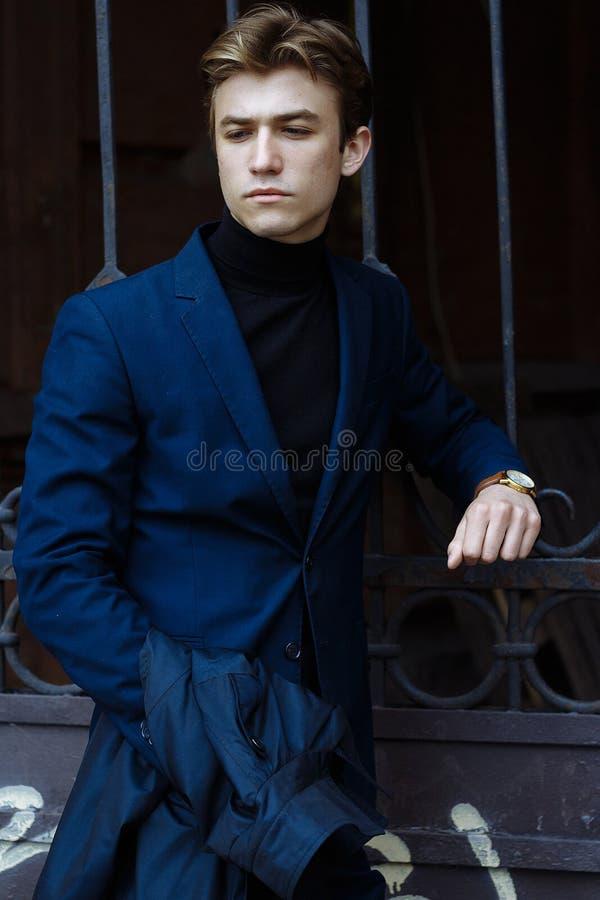 一个可爱的人的画象衣服和一件黑毛线衣的,特写镜头,在他的手上金表,细想姿势,看 库存图片