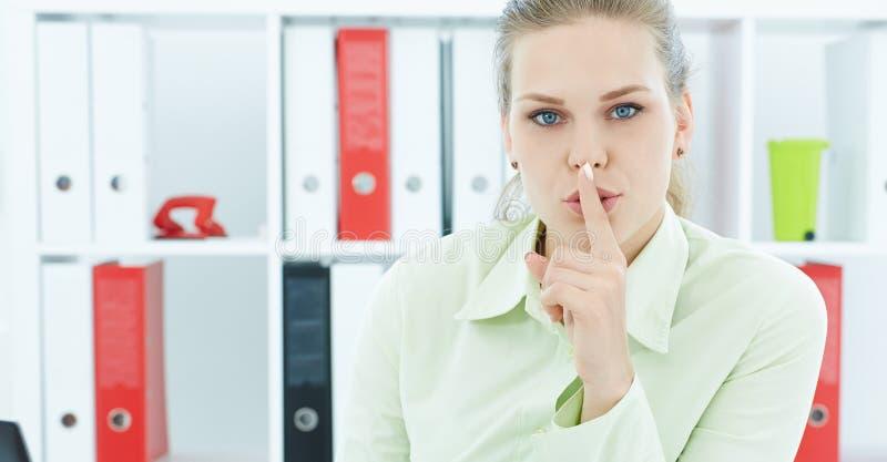 一个可爱的女商人的画象有手指的在嘴唇 年轻女实业家在办公室请求沈默 免版税库存图片