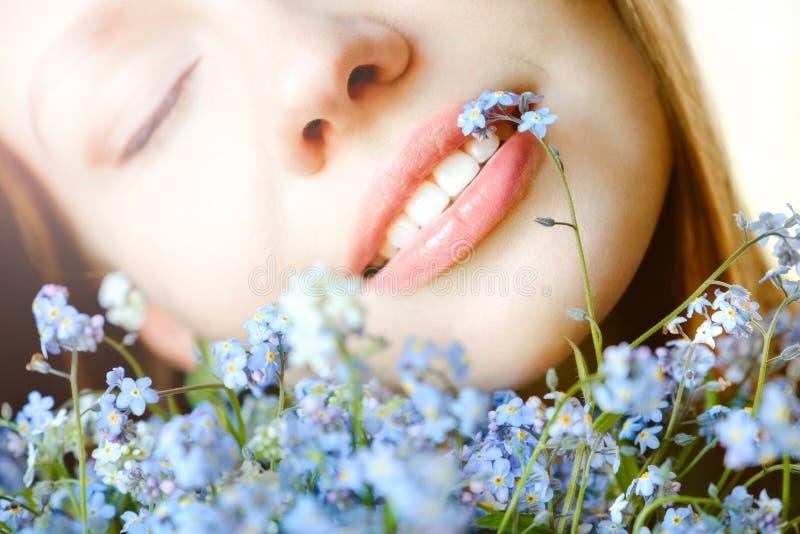 一个可爱的女孩的一张肉欲的画象的特写镜头有勿忘草的 库存图片