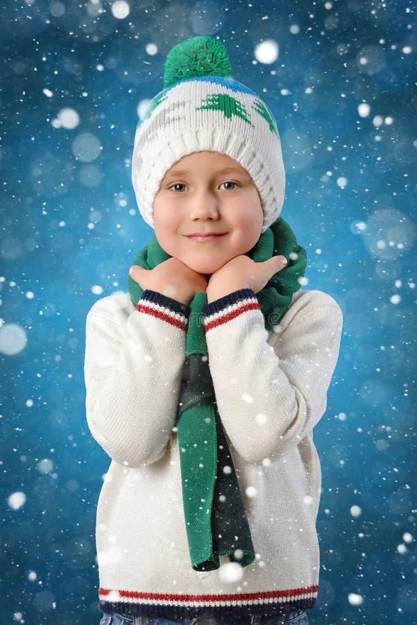 一个可爱的小孩男孩的画象温暖的冬天帽子和围巾的在蓝色背景图画雪花 库存图片