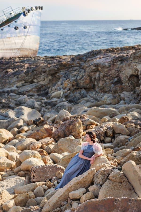 一个可爱的少妇优美地温文地坐等待与在背景的一条被放弃的小船的石头 库存图片