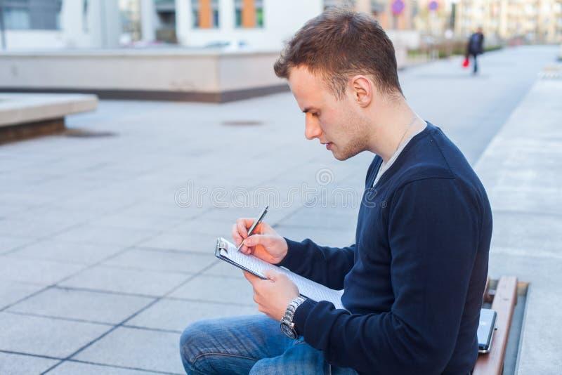 一个可爱的少年男孩的画象坐一个长木凳 图库摄影
