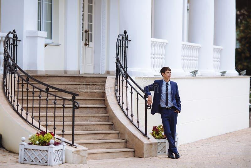 一个可爱的年轻人在一套时髦的衣服,领带走向婚礼,穿戴了,并且等待客人,站立在附近 库存照片
