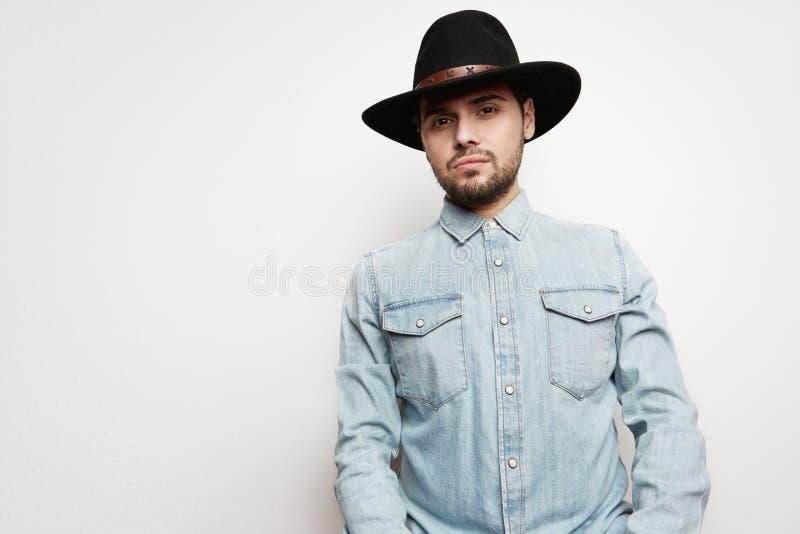 一个可爱的白种人人和在白色背景隔绝的看照相机的画象帽子佩带的牛仔布衬衣的 库存照片