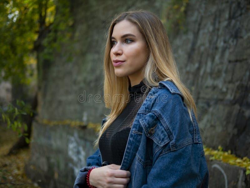 一个可爱的白肤金发的女孩的画象牛仔布夹克的在街道上站立对一个石墙 库存照片
