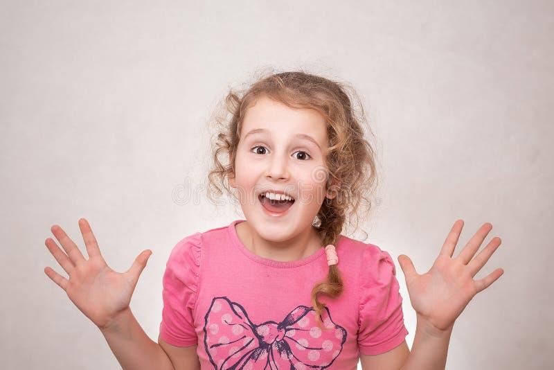 一个可爱的矮小的卷曲女孩的画象,微笑,显示十个项目,隔绝在灰色背景 库存图片