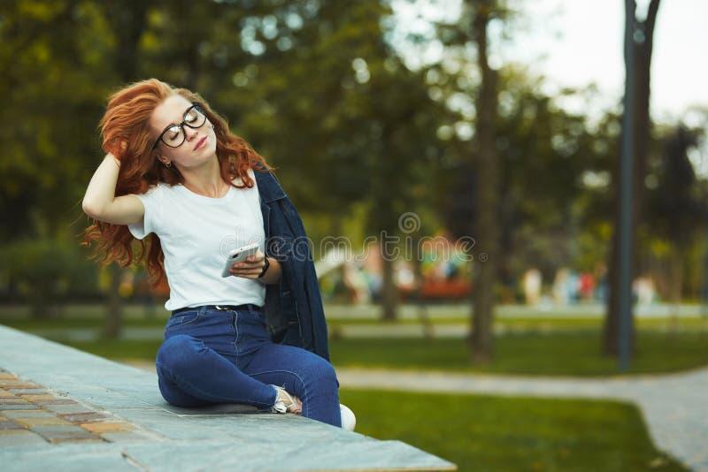 一个可爱的红发女孩坐公园并且为照相机摆在 女孩继续下去有牛仔裤的,玻璃一件T恤杉  图库摄影
