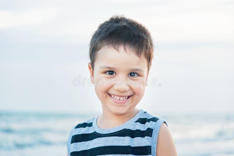 一个可爱的英俊的微笑的男孩的特写镜头画象看照相机的背心的 特写正面面孔,滑稽的逗人喜爱的孩子在 图库摄影