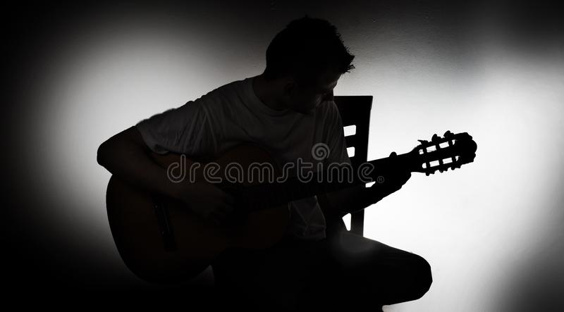 一个吉他弹奏者的剪影有一把声学吉他的坐椅子,黑背景 免版税库存照片