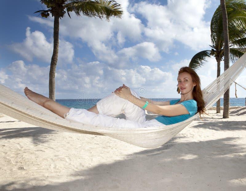 一个吊床的美丽的年轻女人在棕榈树和海背景的海滩  库存照片