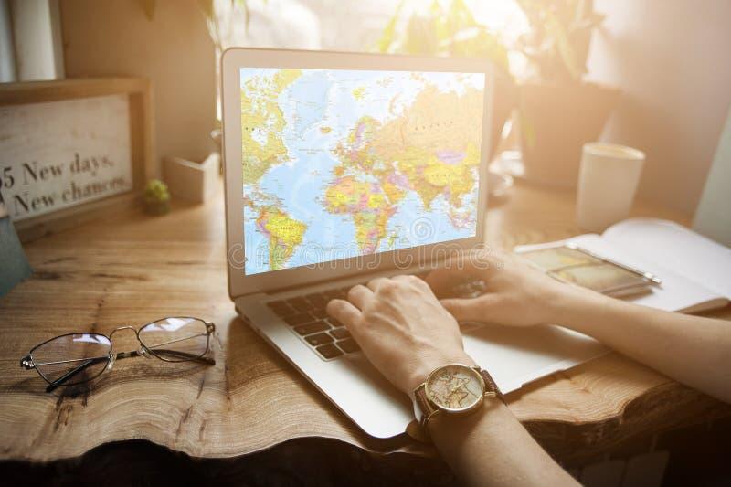 一个咖啡馆的一个旅客女孩与膝上型计算机在世界地图的一次旅途上寻找关于何处的信息飞行 旅行的概念 免版税库存图片