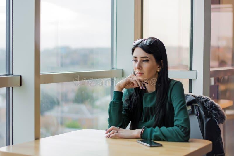 一个咖啡馆的年轻女人在预期调查的桌附近一个大窗口 库存图片