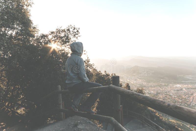 一个哀伤或不快乐的人的画象坐栏杆在日落 库存图片