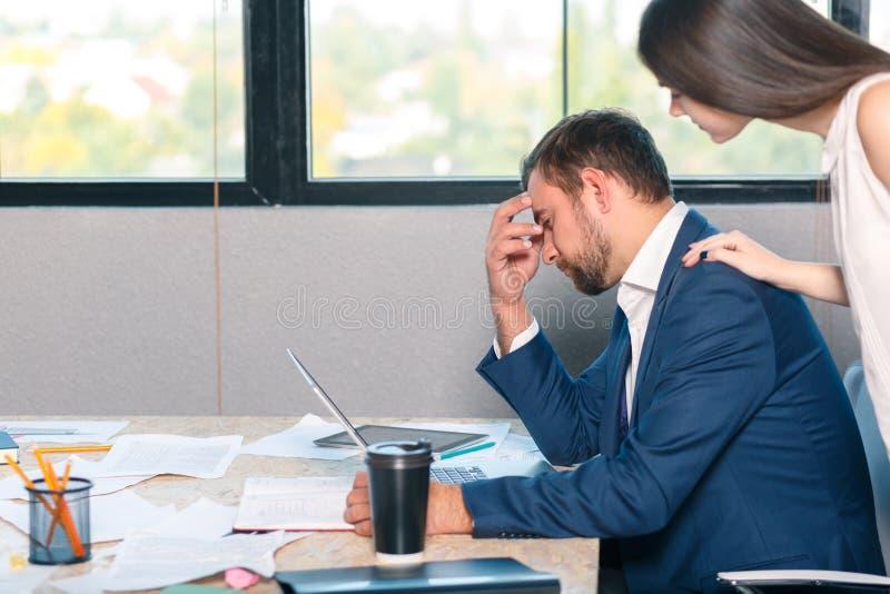 一个哀伤的人坐在书桌并且紧贴到他的头,在他旁边的雇员立场并且安慰他 库存图片