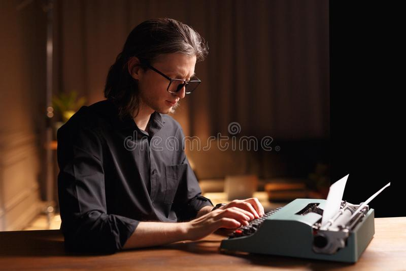 一个哀伤的人的档案镜片的,供以座位在一张木桌上,运作在黑暗内部的一台老葡萄酒打字机 免版税库存照片