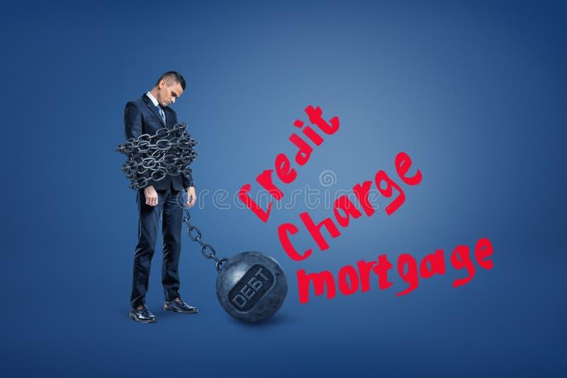 一个哀伤的商人站立一定由与附近红色文字信用、充电和抵押的铁球链子 免版税库存照片