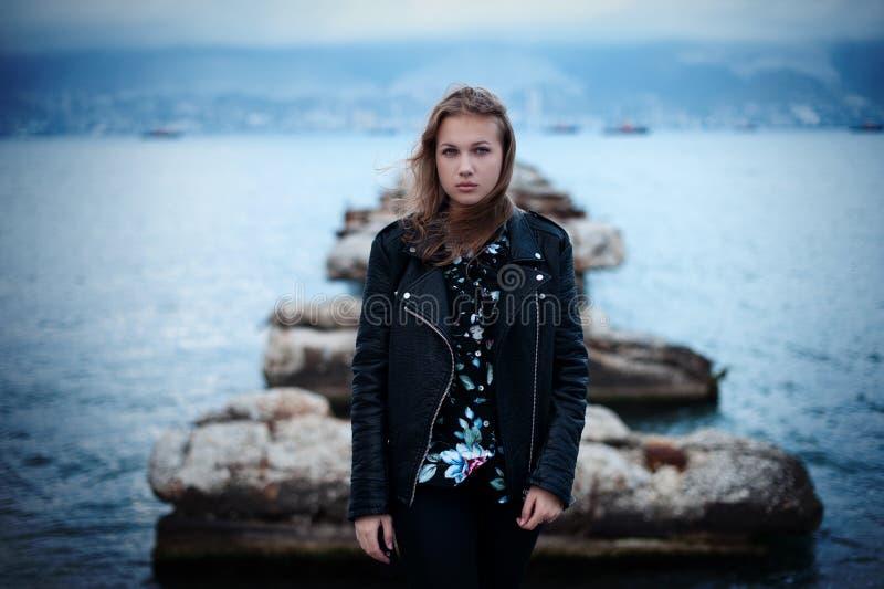 一个哀伤的女孩在海船坞站立 库存图片