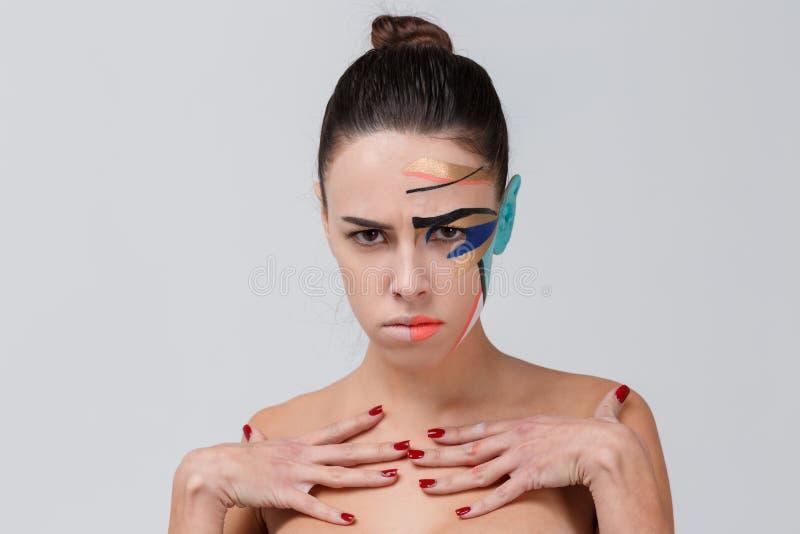 一个哀伤的女孩,有在她的面孔的一种创造性的几何演员化妆用油的 特写镜头 图库摄影