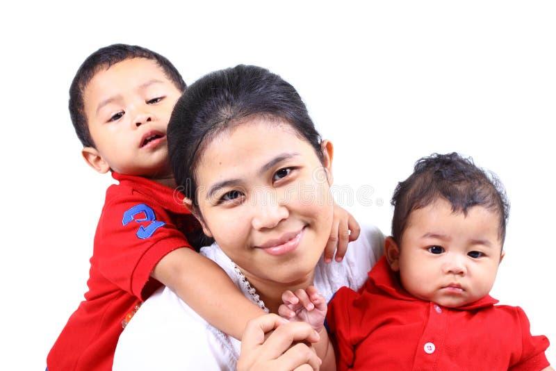 一个哀伤的男孩,微笑的母亲,冷静婴儿。 库存图片