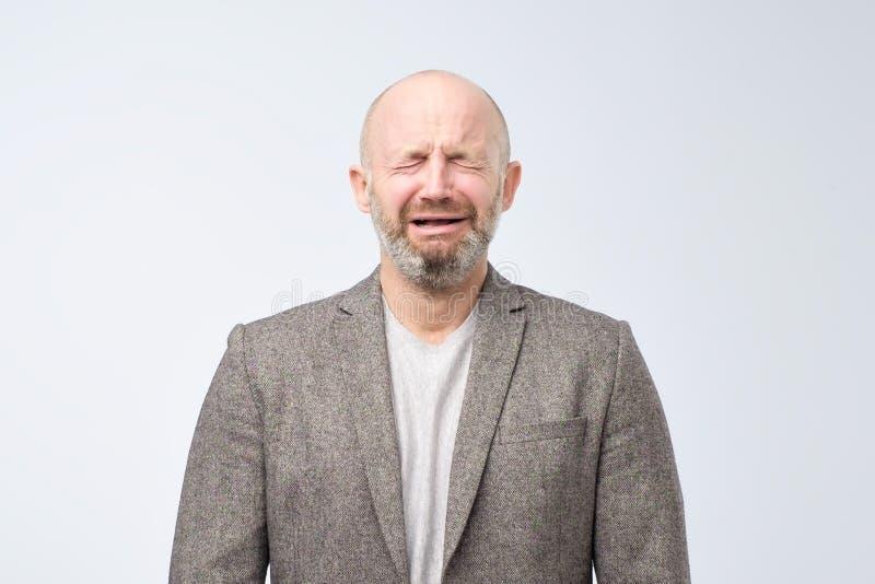 一个哭泣的白种人人和在白色背景的偶然衣服的画象胡子的 免版税库存照片