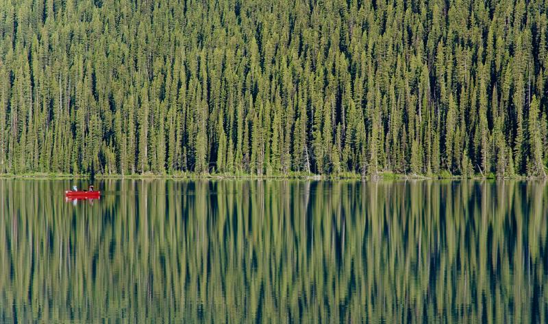 一个唯一红色独木舟在玻璃状路易丝湖漂浮 库存图片