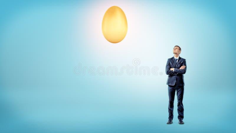 一个商人用横渡的手查寻对顶上一个大光亮的金黄的鸡蛋 库存照片