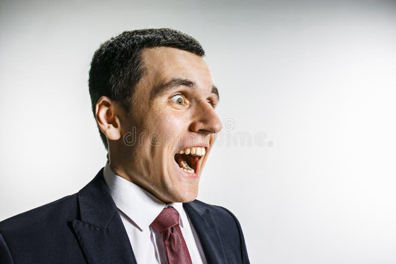 一个商人的四分之三的画象与惊奇的和微笑的面孔的 有穿甲神色的确信的专家 免版税库存照片