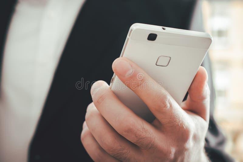 一个商人的宏指令使用一个智能手机的在明亮的背景前面 库存照片