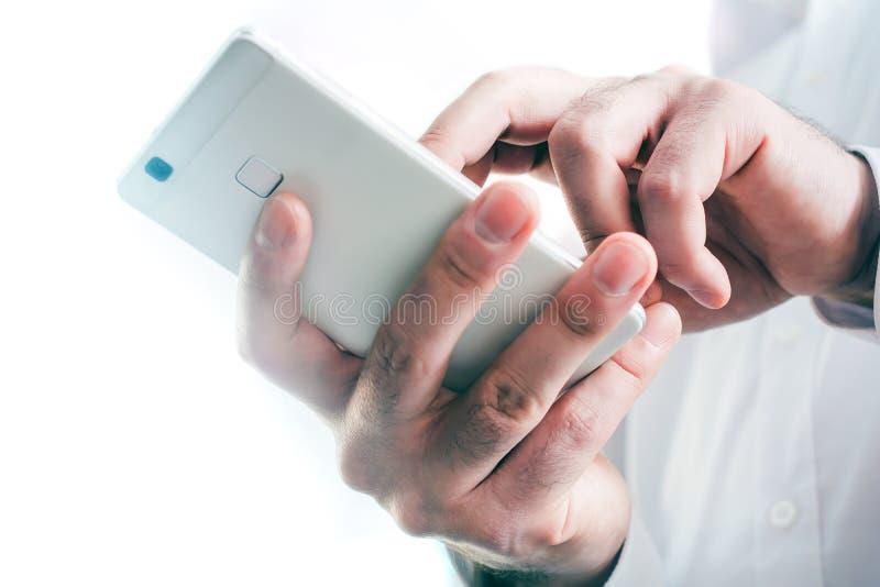 一个商人的宏指令在接触在明亮的背景前面的白色衬衣的一个白色智能手机 免版税库存照片