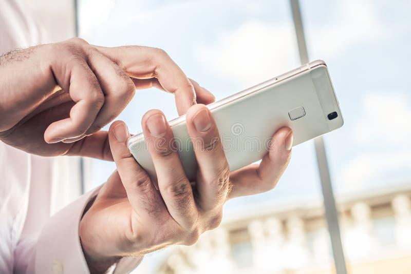 一个商人的宏指令在白色衬衣的使用在明亮的背景前面的一个白色手机 库存图片