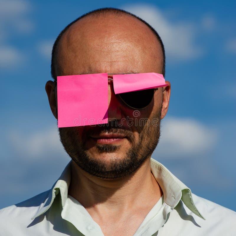 一个商人的概念性画象在被黏贴的现代太阳镜的 库存图片
